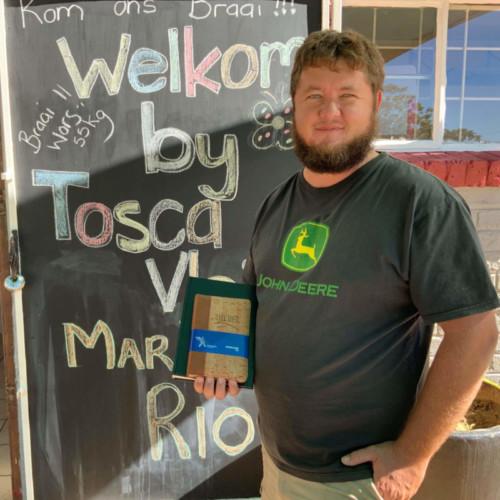 Koos du Plessis is die jongman op Tosca wat die plaaslike slaghuis besit. Hy is ook bekend as die ou wat hom oor die boere in die distrik ontferm en gereeld uitry om te kyk 'of die ooms nog okei is.' Hier is Koos voor sy slaghuis met die Bybels wat CLF as geskenkies vir die boere saam gestuur het.